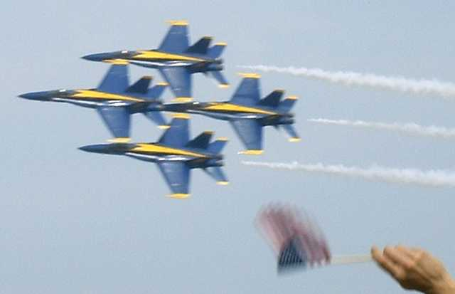 Blue Angels in a diamond formation, with American flag in foreground